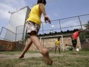"Children play soccer in the Vila Autodromo slum in Rio de Janeiro, Brazil, July 28, 2015. As sports arenas rise up around them and neighbours' houses are demolished, around 50 families remain in Vila Autodromo, a favela bordering the Olympic Park in Rio de Janeiro. About half of those refuse to leave the favela, which they describe as ""paradise"" because of a lack of violence compared with poor areas elsewhere in the city. With a year until the Games come to Brazil, over 90 percent of residents have already left after accepting compensation. The holdouts, despite violent run-ins with police, vow to fight eviction whatever the cost. Living in a ghost town with sporadic access to water and electricity, the families have become a symbol against the use of the Olympic Games to modernize Rio, a move critics say is only benefiting the rich. REUTERS/Ricardo Moraes TPX IMAGES OF THE DAYPICTURE 6 OF 28 FOR WIDER IMAGE STORY ""FIGHTING OLYMPIC EVICTION IN RIO FAVELA"" SEARCH ""RICARDO PARADISE"" FOR ALL IMAGES 'Ä® TPX IMAGES OF THE DAY - RTX1Q0DR"